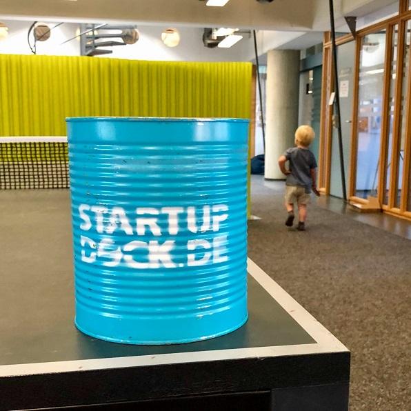 """Foto aus dem Startup-Dock Hamburg mit einer Dose mit Beschriftung """"Startup Dock"""" auf einer Tischtennisplatte mit Kind im Hintergrund"""