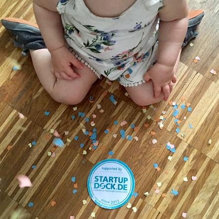 Kleinkind sitzt vor Logo SUpported By Startup Docl Gründen an Hamburger Hochschulen mit Konfetti